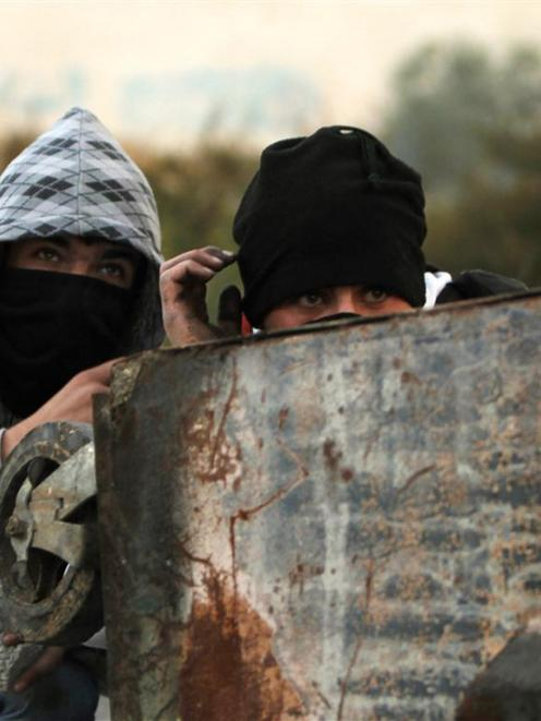 Palestinian stone-throwers take cover behind a garbage bin during clashes with Israeli security...
