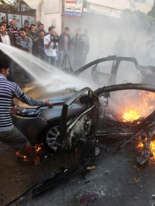 Palestinians help extinguish the fire after an Israeli air strike on the car of Hamas's top...