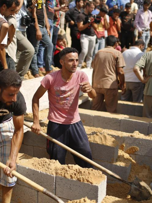 Palestinians prepare the graves for eight members of the Abu Jarad family, including three...