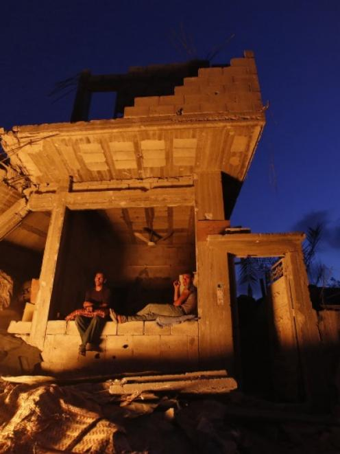 Palestinians sit outside their house that witnesses said was heavily shelled by Israel during the...