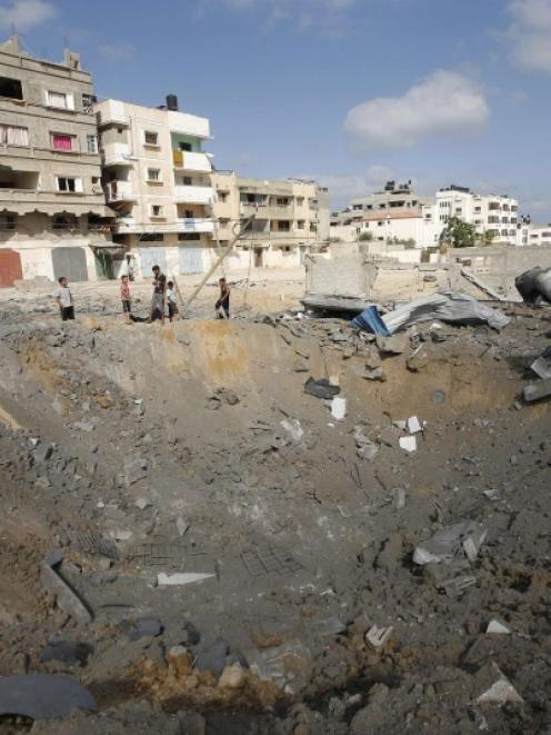 Palestinians stand next to a crater which police said was caused by an Israeli air strike in Gaza...