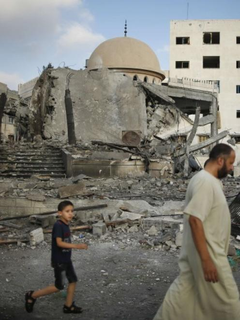 Palestinians walk past the ruins of a mosque, which police said was hit in an Israeli air strike,...