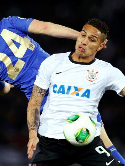 Paolo Guerrero (R) of Corinthians fights for the ball with Gary Cahill of Chelsea during their...