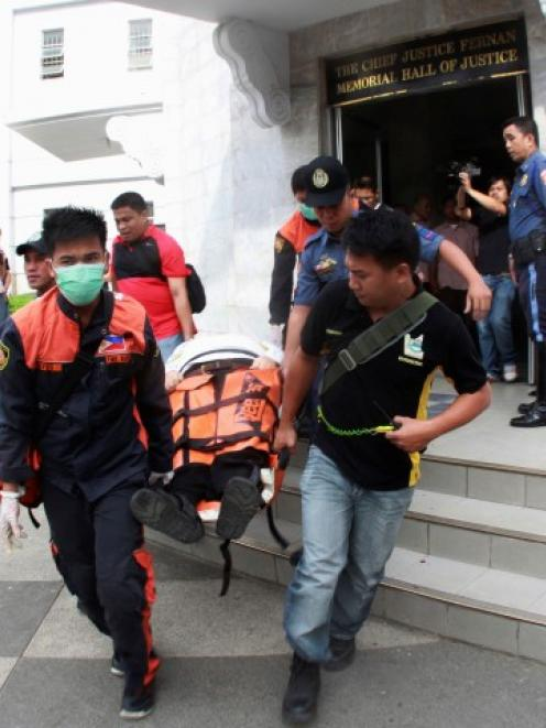 Paramedics and police carry on a stretcher the body of John Pope outside a courtroom in Cebu city...