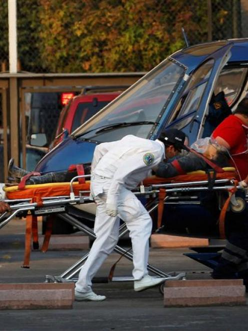 Paramedics wheel an injured person to a helicopter at the parking lot of the state-run oil...
