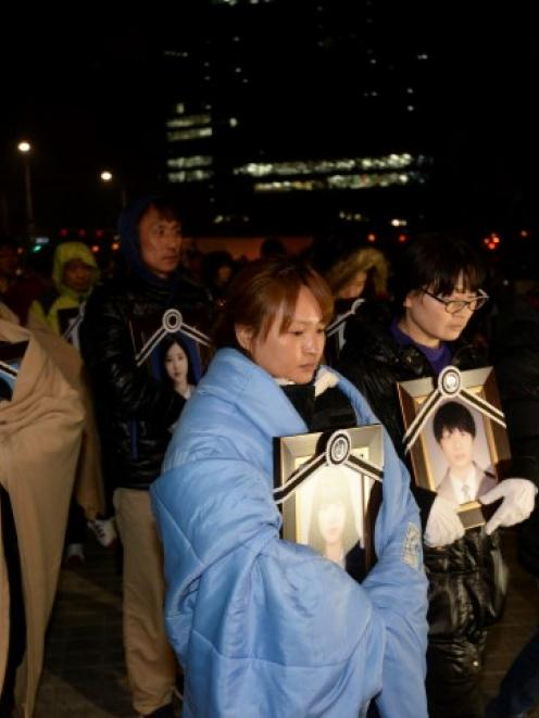 Parents holding portraits of their children, who died on sunken passenger ship Sewol, march...