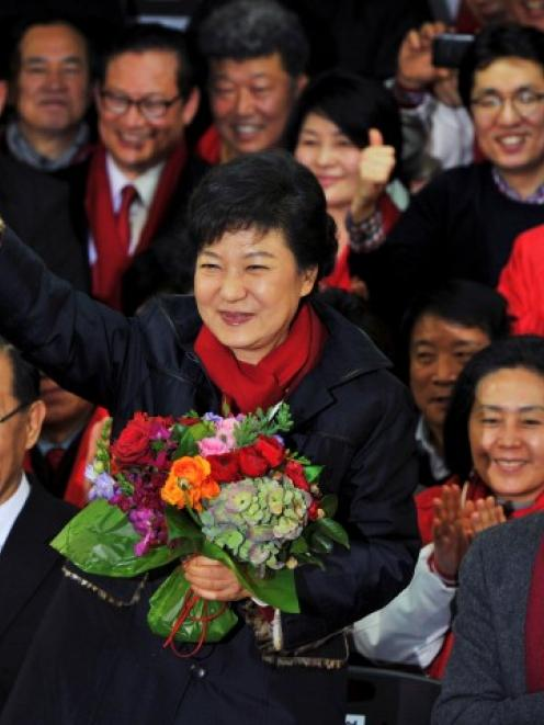 Park Geun-Hye waves as she holds a bouquet of flowers after arriving at the headquarters of the...