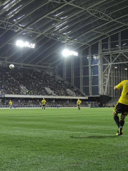 Part of the 15,000 crowd watches Leo Bertos taking a corner for the Wellington Phoenix against...