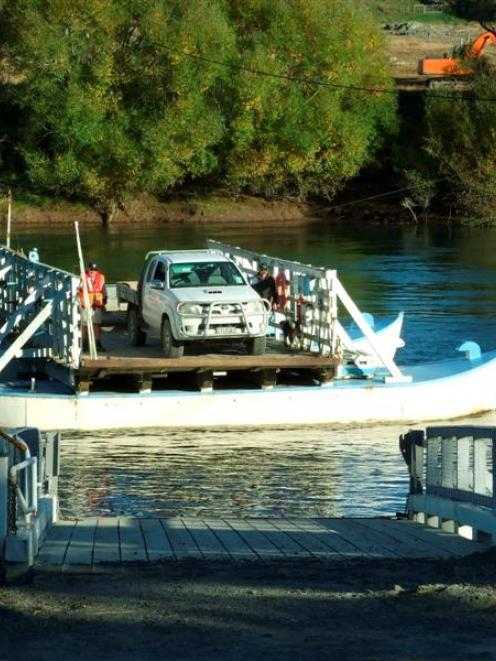 Part-time punt operator Neil Sowry (left) takes Gary Stirling and his ute across the Clutha River...
