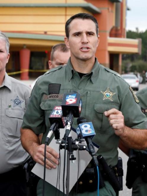 Pasco County Sheriff Chris Nocco (C) speaks to the media near the Cobb Grove 16 movie theatre...