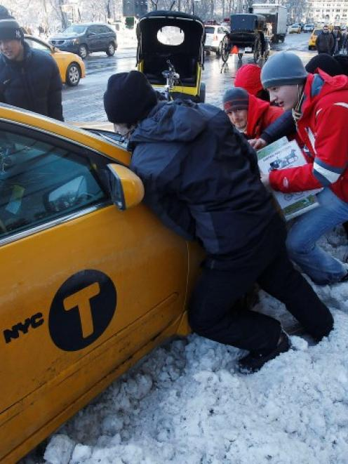 Passersby help push a taxi out of a snow drift in New York after a blizzard pummelled the...