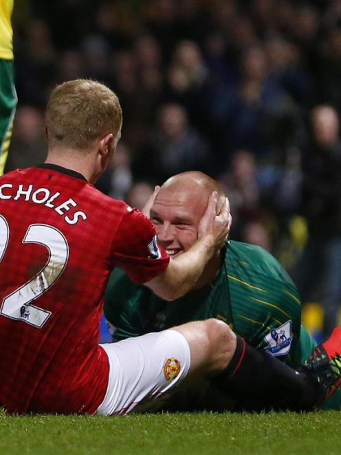 Paul Scholes, of Manchester United, with Norwich goalkeeper John Ruddy at the end of the game...