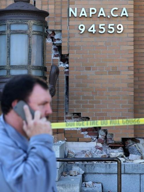 Pedestrians walk by the damaged Napa post office following the earthquake.  (Photo by Justin...
