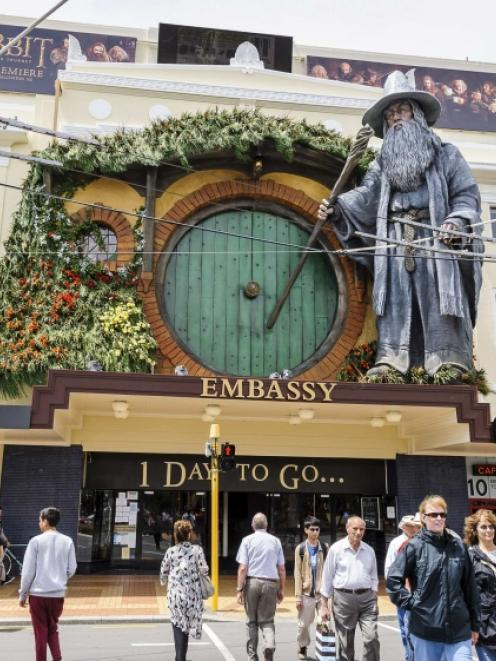 Pedestrians walk past a giant model of the J. R. R. Tolkien character Gandalf mounted on the...