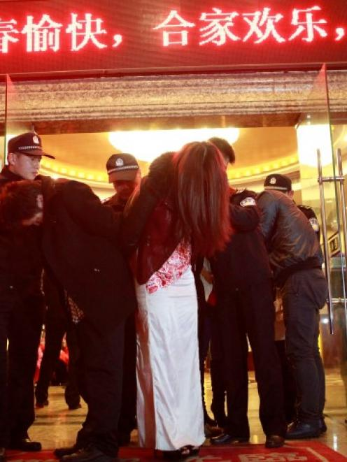 People are taken away during a police raid at a hotel, as part of the crackdown on prostitution...