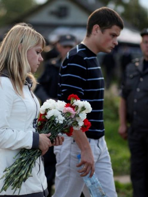 People bring flowers to the site of a plane crash that killed 43 people near the Russian city of...