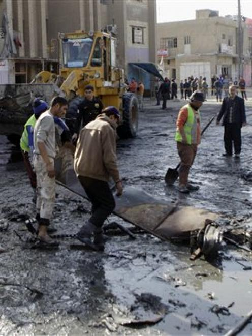 People clean the scene of a car bomb attack in Zafaraniyah, Baghdad, in which 33 people were...