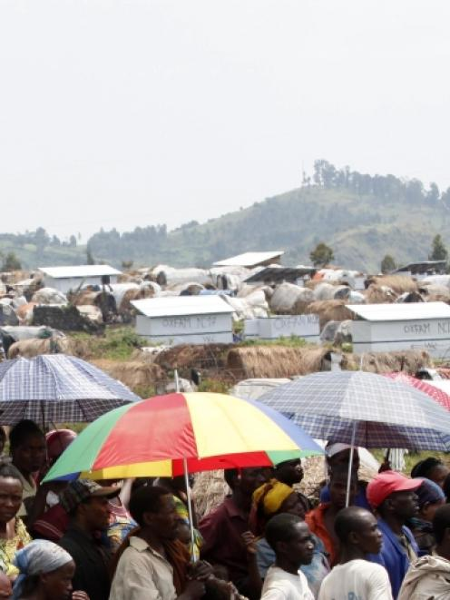 People displaced by recent fighting in eastern Congo wait to receive aid food in Mugunga IDP camp...