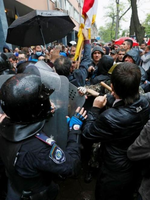 People gather in front of Ukrainian Interior Ministry security forces members who form a cordon...
