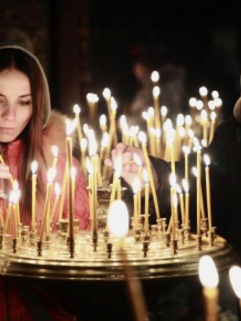 People light candles during a religious service at a church in Kiev.  REUTERS/David Mdzinarishvili