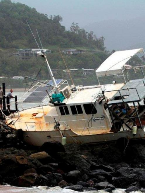 People look at a boat that was washed up on to rocks at Airlie Beach about 120km southeast of...