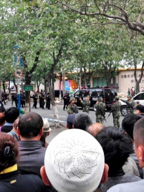 People look on at a street cordoned off by police after one of the blasts in Urumqi. REUTERS...