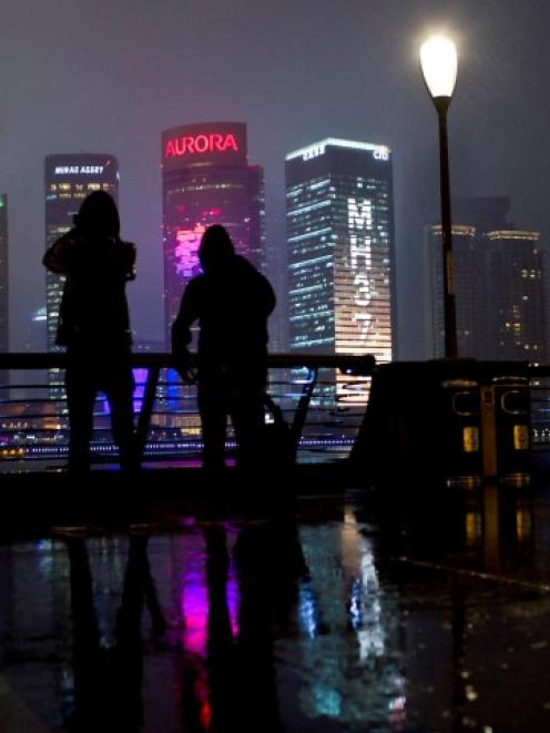 People on the Bund look at a building with lights forming the words MH370, the flight number of...