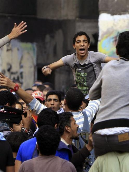 People protest to mark the one-year anniversary of fatal clashes on Mohamed Mahmoud Street, near...