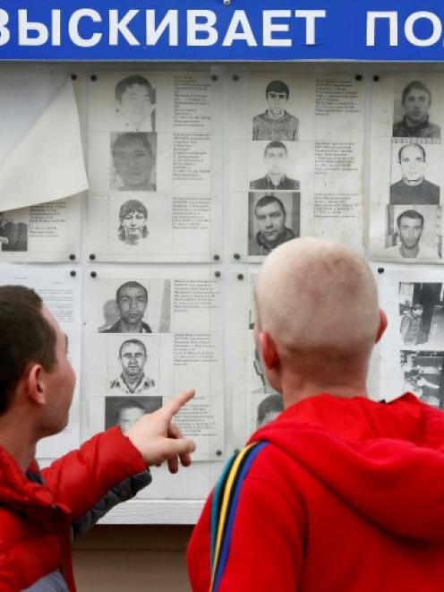 People stand in front of a board with mugshots of wanted people in the Adler district of Sochi....