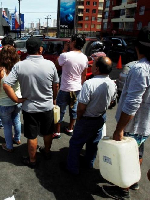 People stand in line to buy fuel in the northern port of Iquique after the earthquake. REUTERS...