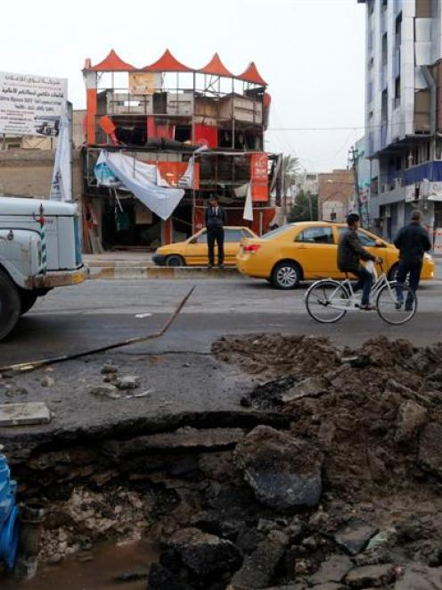 People the site of a car bomb attack in Baghdad's Karaada district.  REUTERS/Thaier al-Sudani