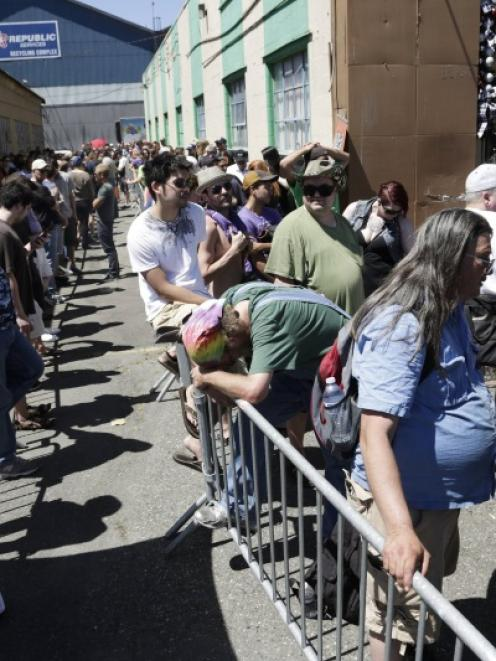 People wait in the heat to enter Cannabis City during the first day of legal retail marijuana...