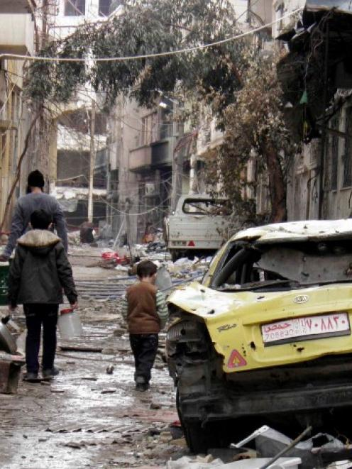 People walk past a damaged car along a damaged street in the besieged area of Homs. REUTERS/Thaer...