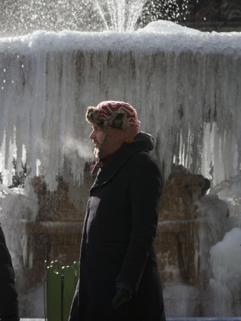 People walk past an ice covered Josephine Shaw Lowell Memorial Fountain, in frigid temperatures...