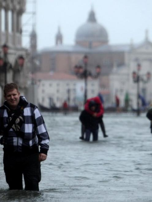 People walk through a flooded street in Venice where the water level has risen to 149cm above...