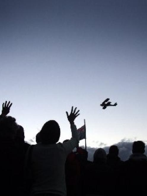 People wave to a Tiger Moth pilot during a flyover at the Lake Hawea Anzac Day dawn service in...