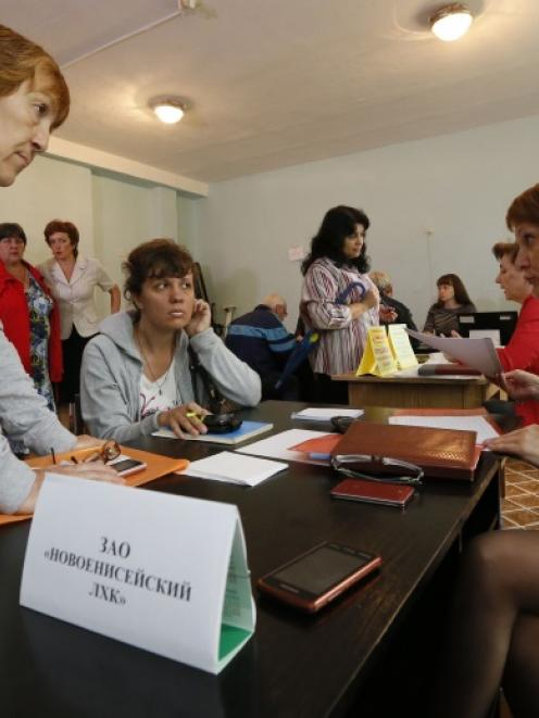People, who have fled the fighting in the eastern regions of Ukraine, queue for job vacancies at...