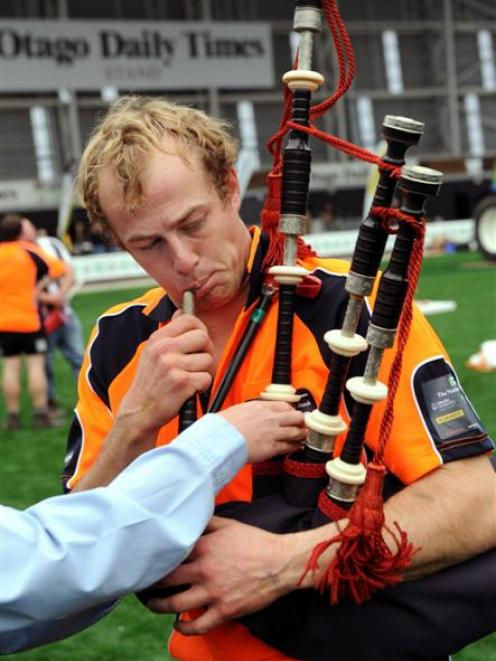 Pete Gardyne tries to inflate a balloon using bagpipes at the conclusion of the Agri-Sports...