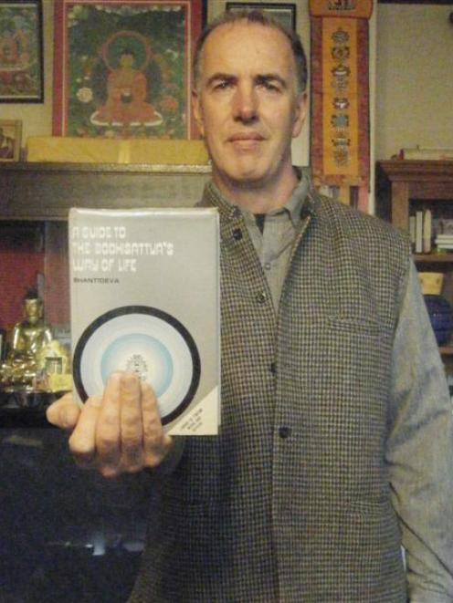Peter Small with the Guide to the Bodhisattva's Way of Life by Shantideva. Photo by Nigel Benson.