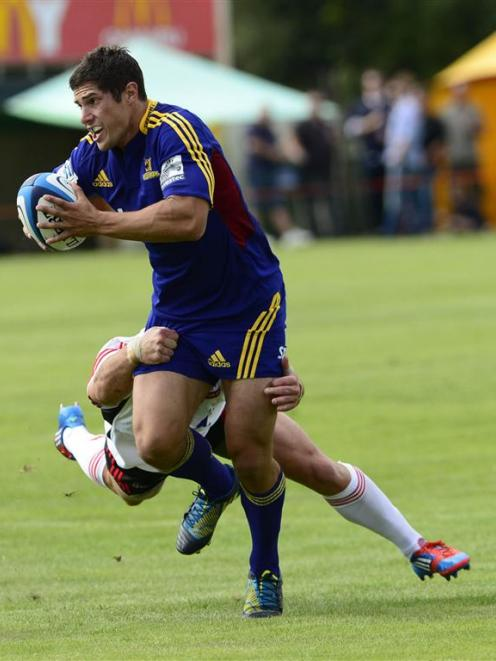 Phil Burleigh of the Highlanders tries to break a tackle. Photo by Peter McIntosh