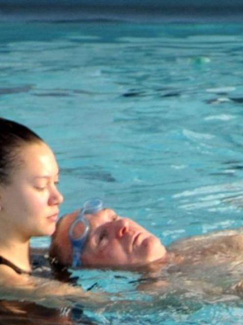 Physiotherapy student Jess Chicksen assists paraplegic Jim Duncan, who was swimming with his wife...