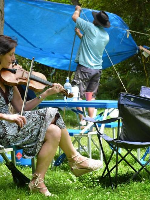 Playing a Scottish tune on the fiddle, performer Anna Bowen takes a break while her husband...