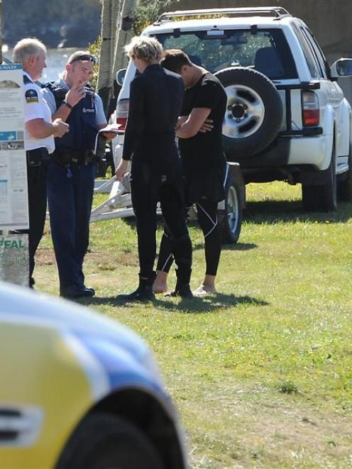 Police and ambulance staff speak to a group of men at Taieri Mouth after their boat flipped when...
