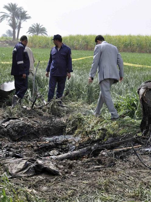 Police and rescue officials check the wreckage of a hot air balloon that crashed in Luxor. ...