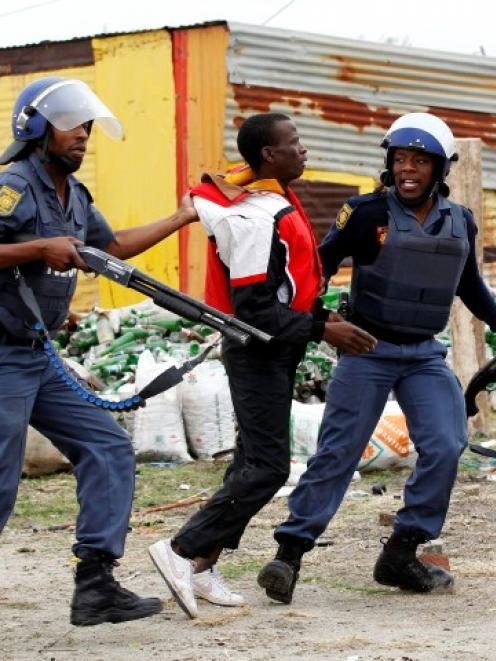 Police arrest a man at Lonmin's Marikana mine in South Africa's North West Province last year....