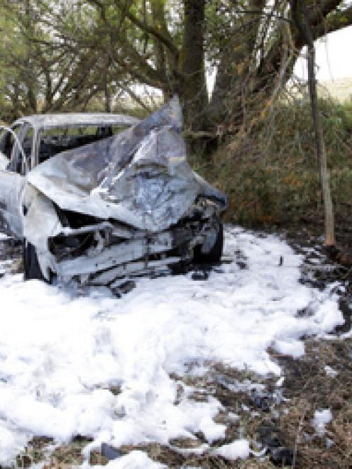 Police at the scene of yesterday's fiery crash near Waipukurau after fire crews had doused the...