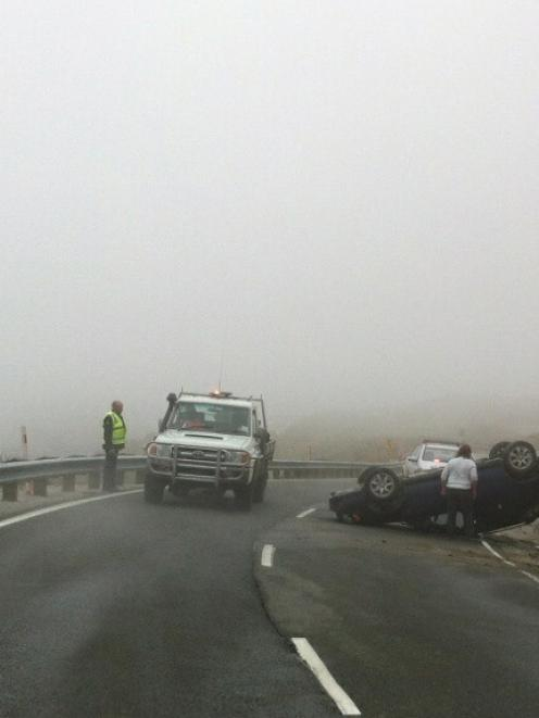 Police at the scene where a car overturned on the Crown Range road today. Photo: Bruce Quirey