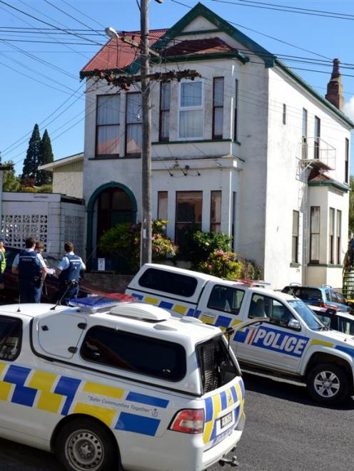 Police cars line the road outside a Duncan St, Dunedin, house where a female occupant was...