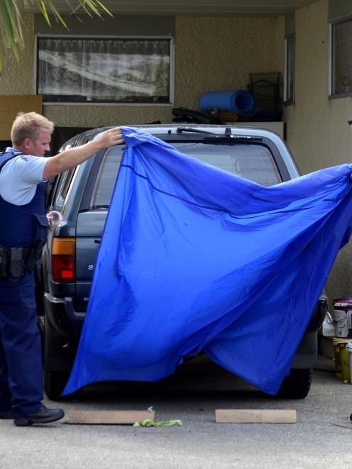 Police cover the Toyota 4WD involved in the alleged abduction of a 2-year-old Dunedin girl from...
