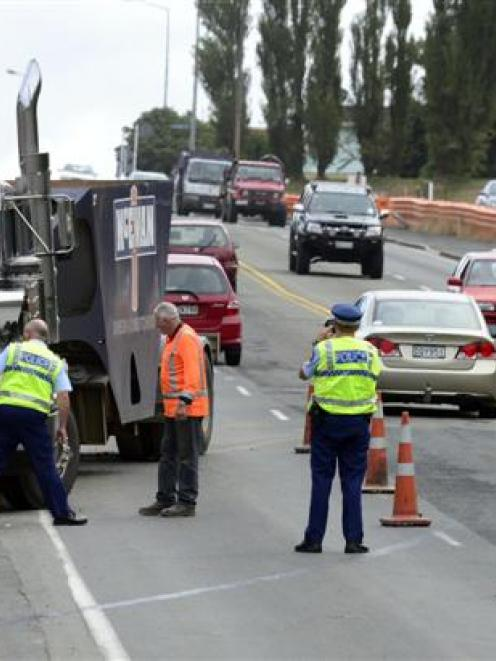 Police inspect a commercial truck after it rolled into a retaining wall beside the south-bound...